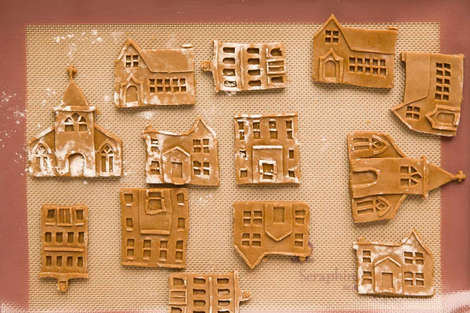 Unbaked gingerbread biscuits in the shape of small houses and churches. They are on top of a baking tray.