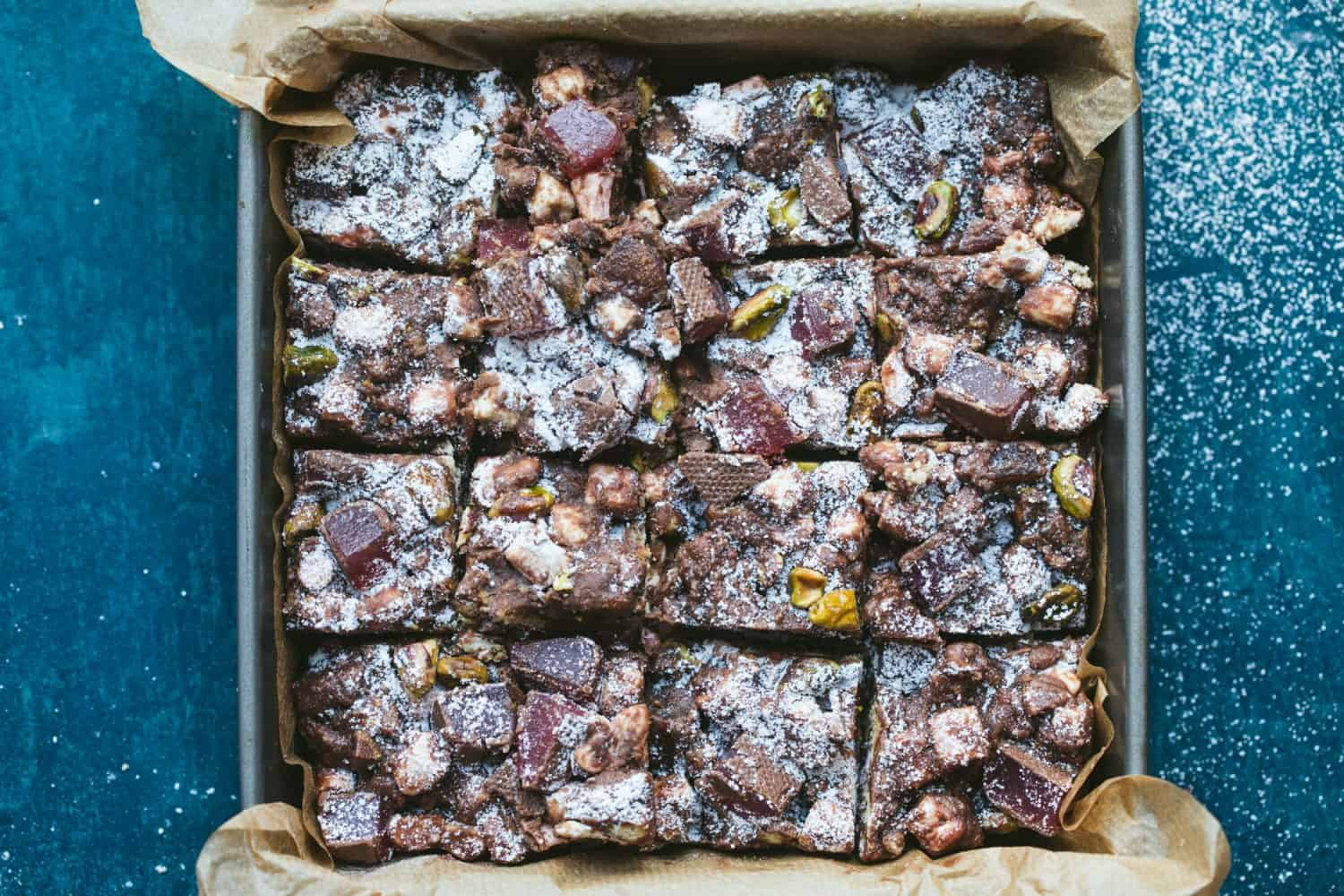 16 squares of chocolate Rocky Road in a baking tray lined with baking paper.