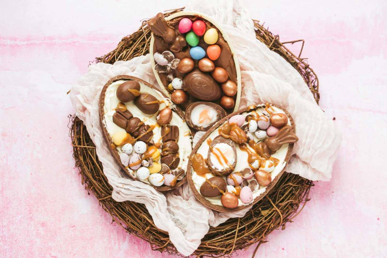 An Easter nest with 3 halves of chocolate Easter eggs on top filled with dessert and creme eggs.