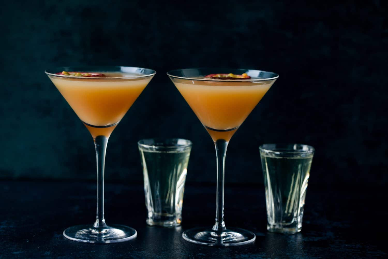 Two martini glasses filled with an orange coloured cocktail and two shot glasses filled with prosecco.