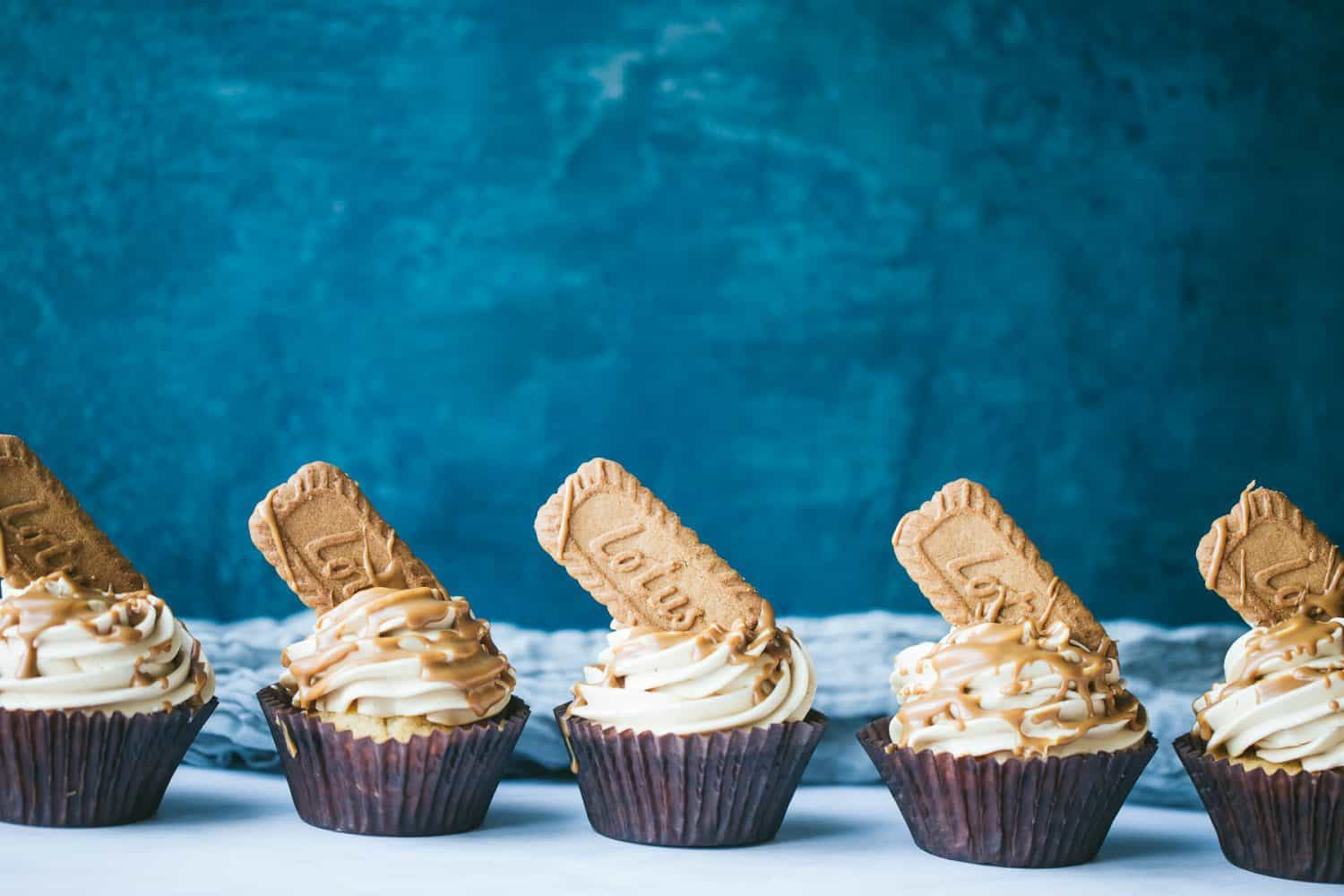 A row of five cupcakes in front of a dark blue background.