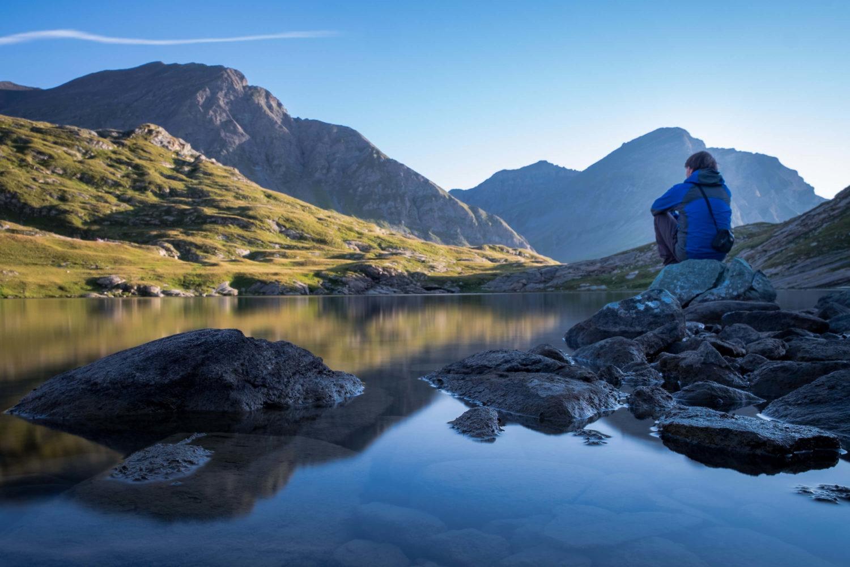 Christopher Püschel sitzt beim Sonnenaufgang an einem See