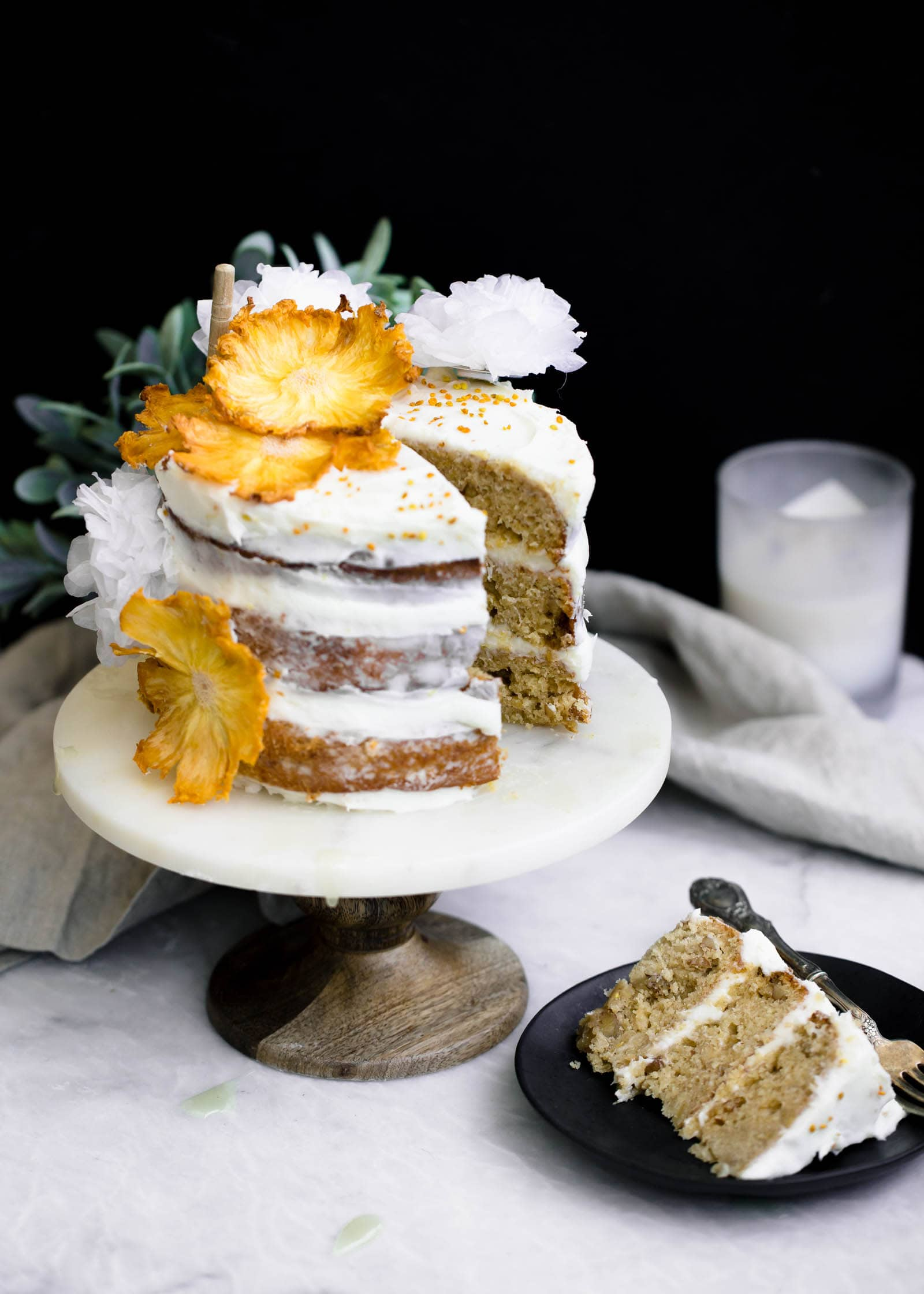 Hummingbird Cake slice on a plate next to cake stand