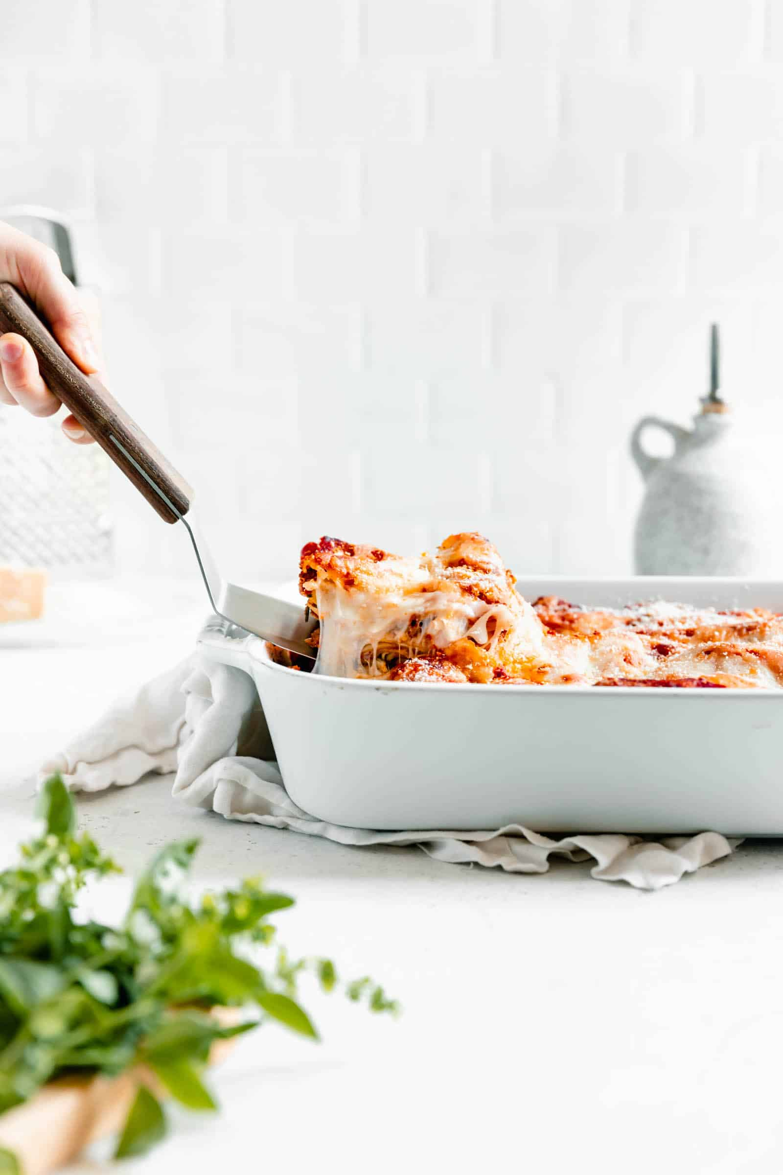 Classic homemade meat lasagna piece lifted out of pan with cheese pull