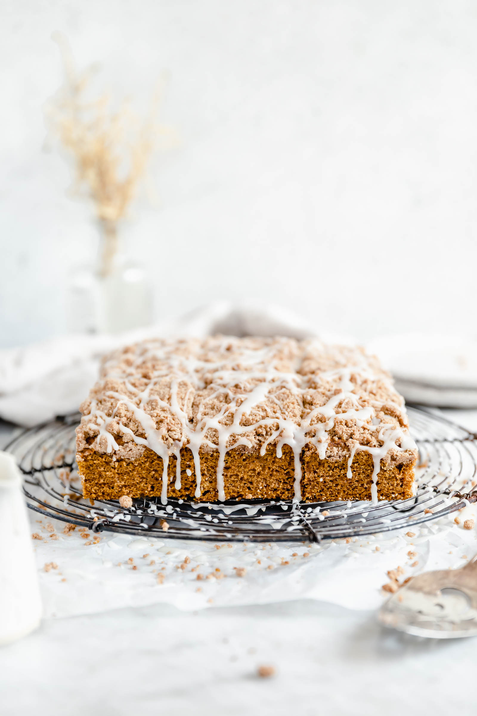 pumpkin coffee cake with crumb topping and cream cheese glaze on a cooling rack