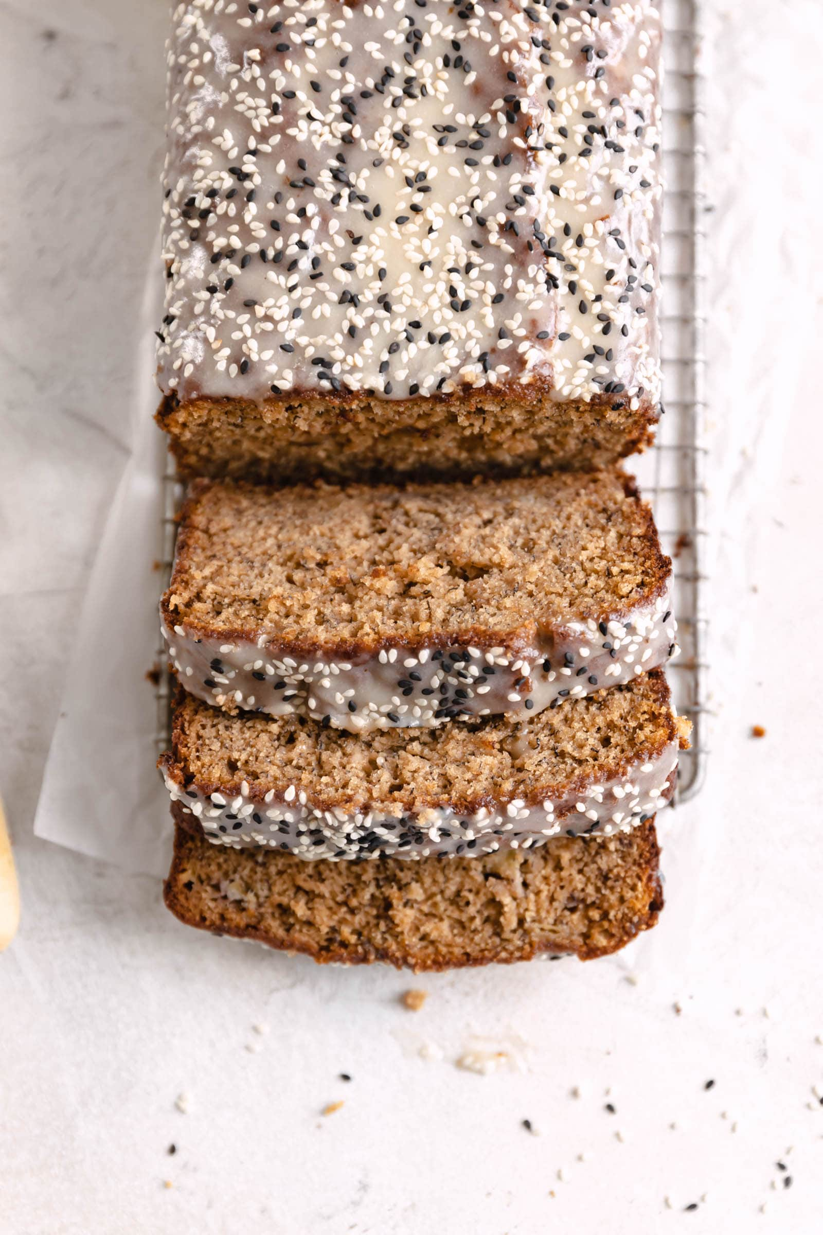 tahini banana bread topped with tahini glaze and sesame seeds