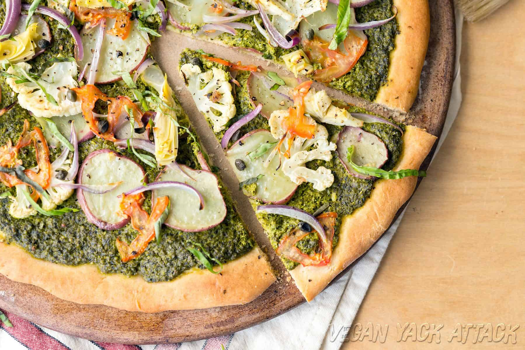 Close up shot of pesto potato pizza with slice cut out