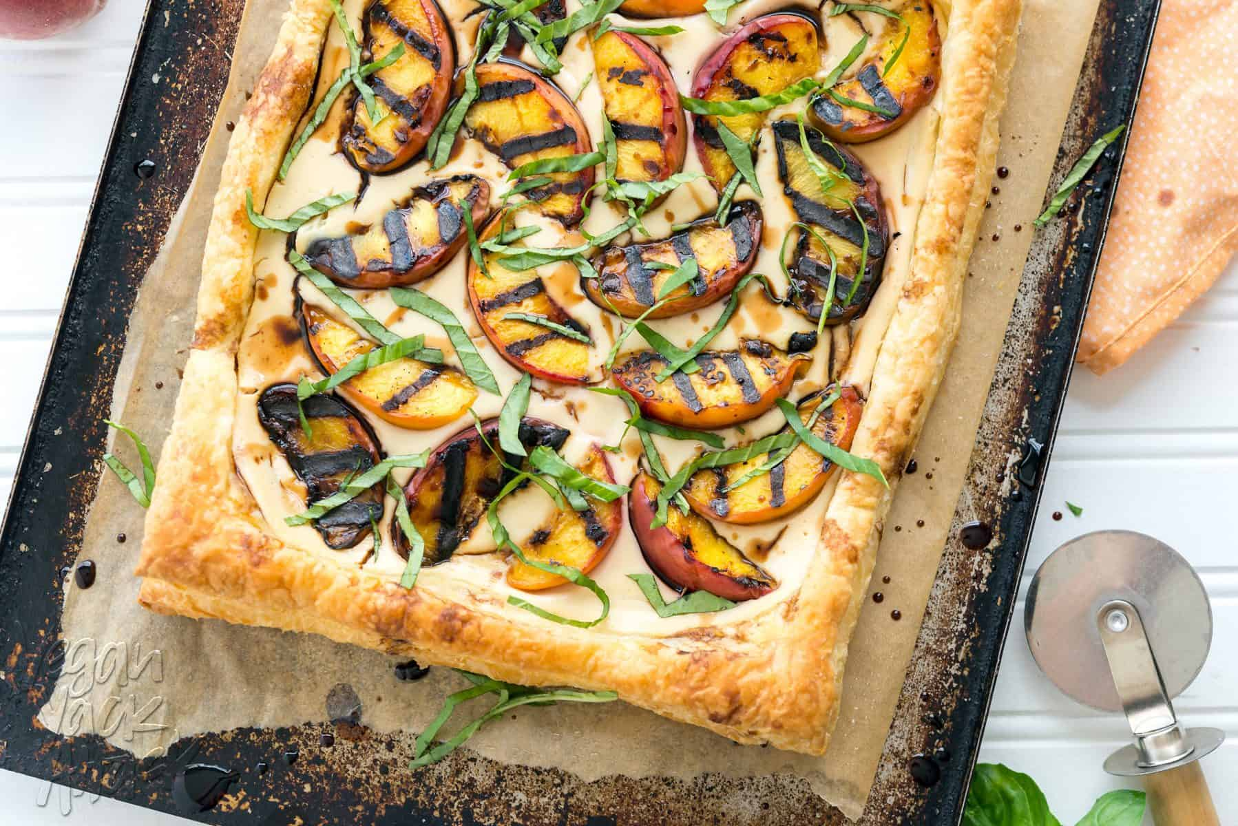 Grilled peaches and cream pastry on a baking sheet lined with parchment paper