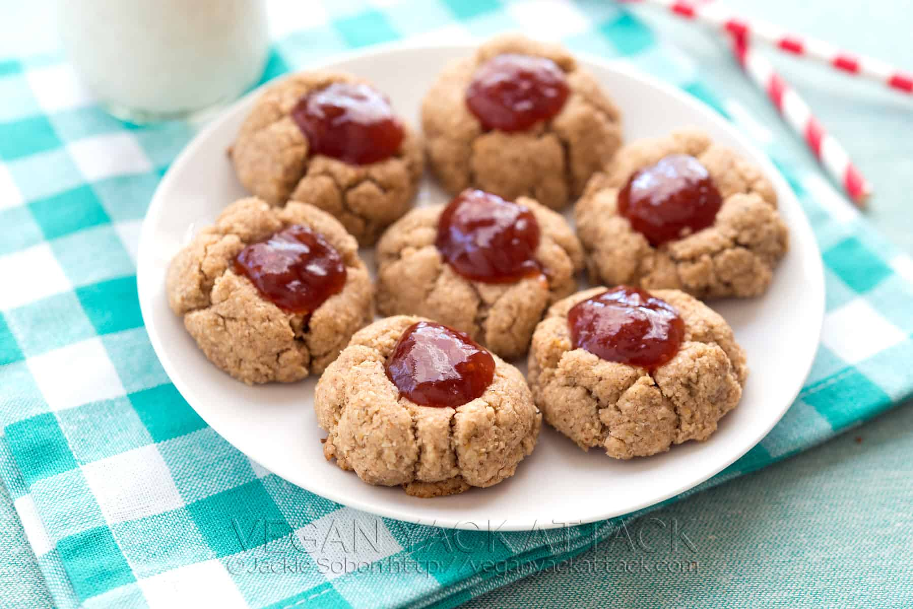 Almond butter jam thumbprint cookies on a white plate on a teal, checkered napkin
