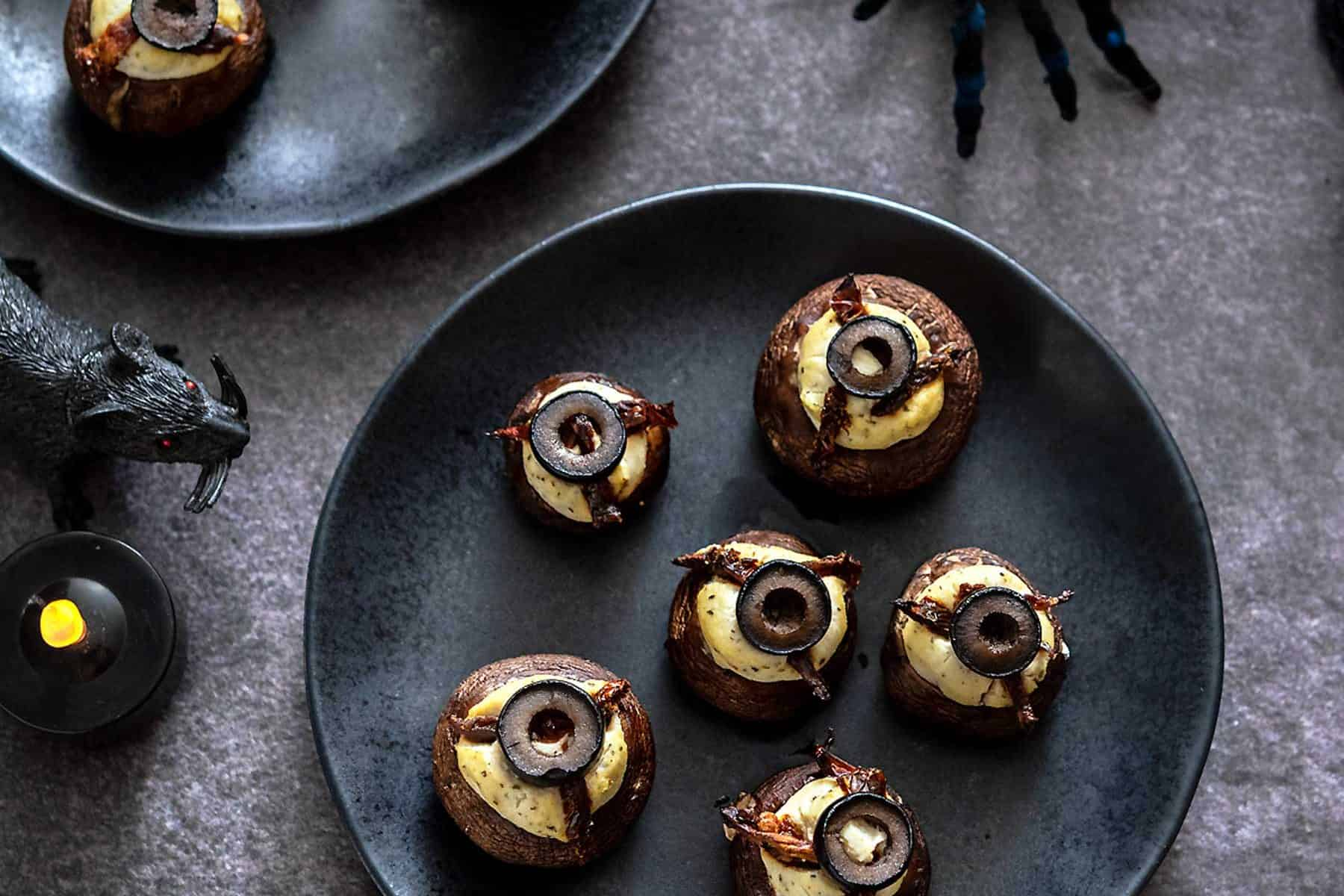 Tofu-Stuffed mushrooms on black plates with halloween decorations