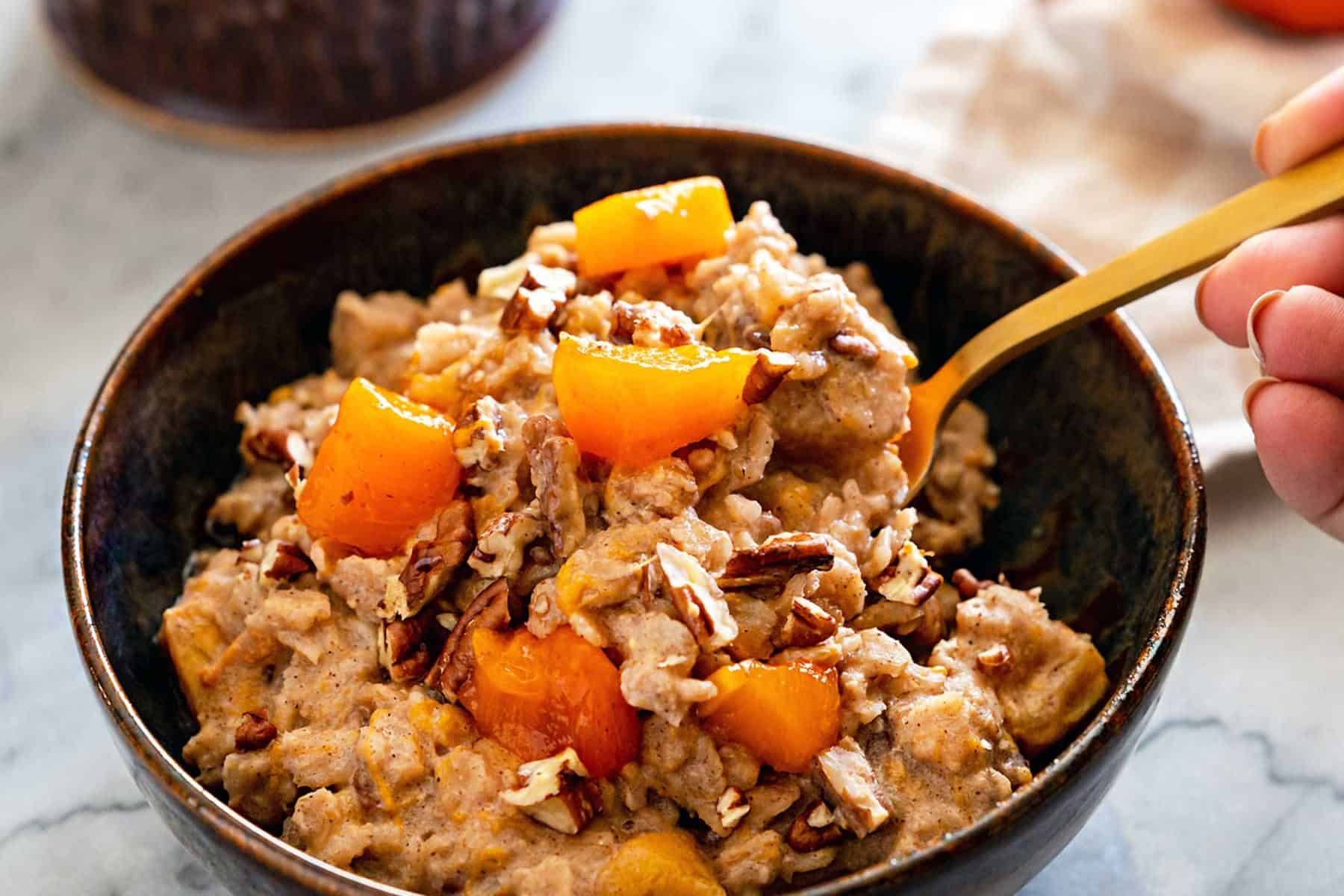 Ceramic bowl filled with persimmon oatmeal, and golden spoon, with a cup of coffee