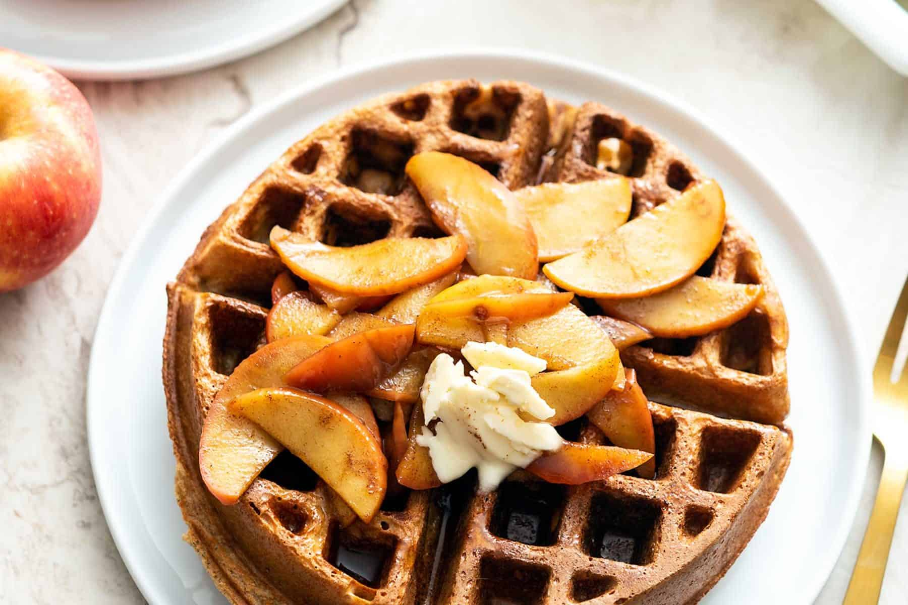 2 large, round, Belgian waffles on white plates, topped with apples and with syrup on the side