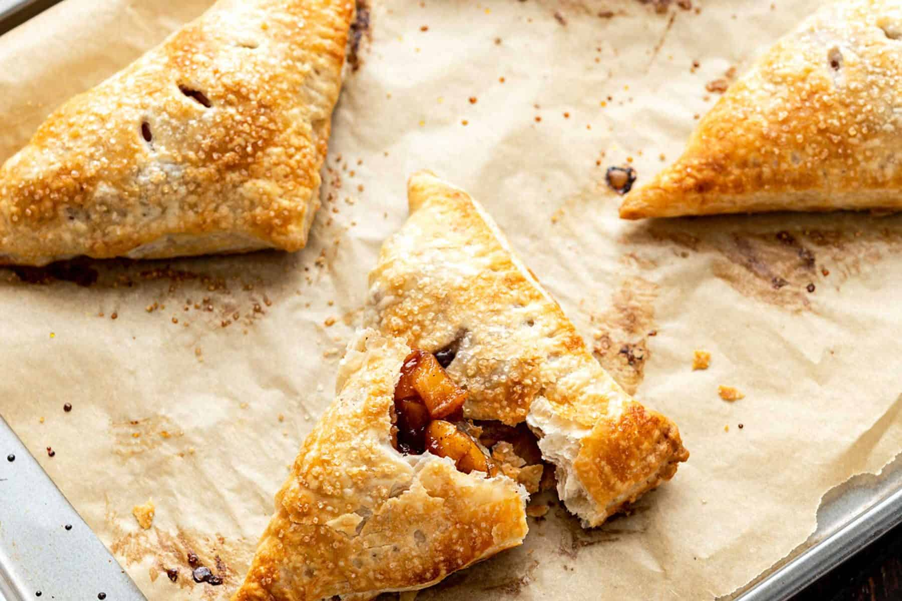 Four apple turnovers on a paper-lined baking sheet with apples