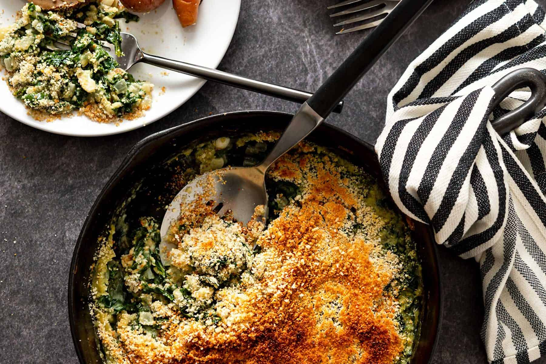 Serving spoon in a cast iron skillet filled with creamed kale next to dinner plates