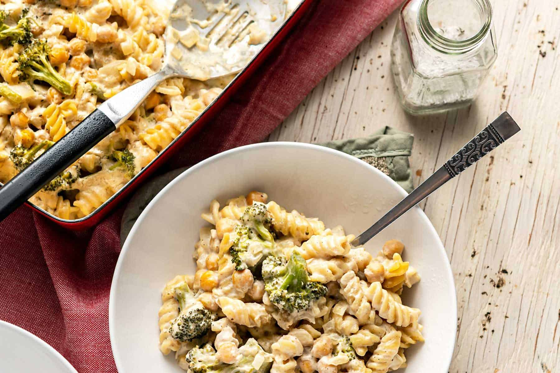 Bowl of No-Boil Broccoli Pasta Bake next to a casserole dish