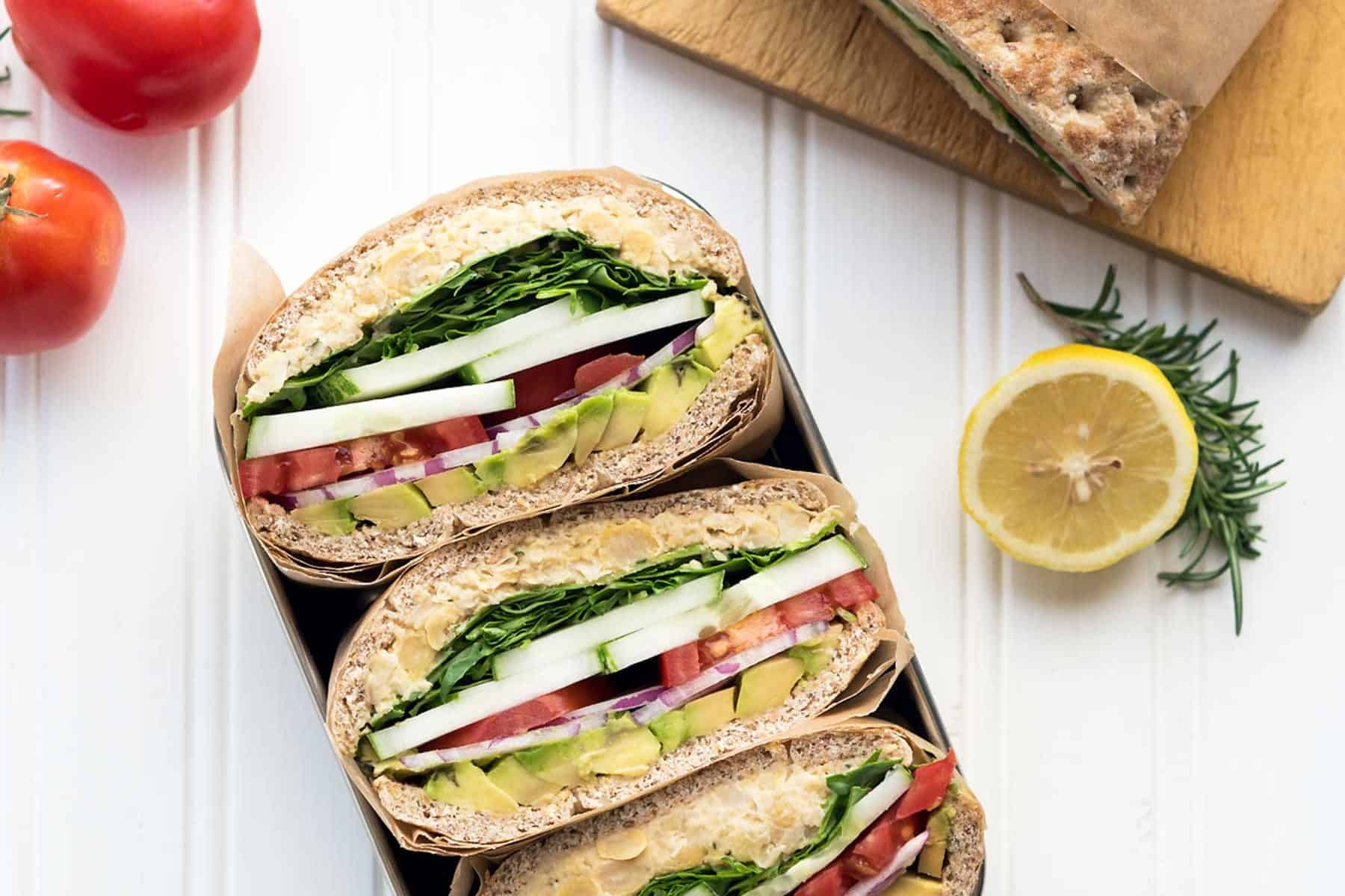Sliced rosemary chickpea salad sandwiches in a lunch container on a white background