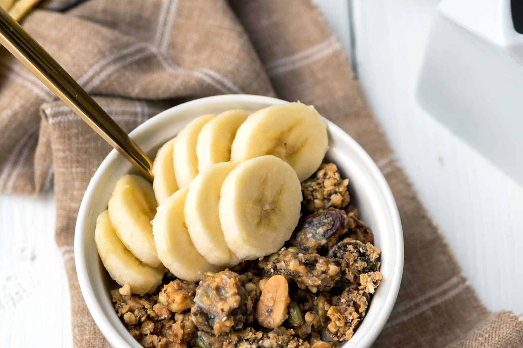 Image of granola in a white bowl with banana slices, over a brown linen