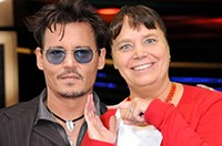 A Las Vegas green screen photo booth featuring a participant posing for a selfie with Johnny Depp