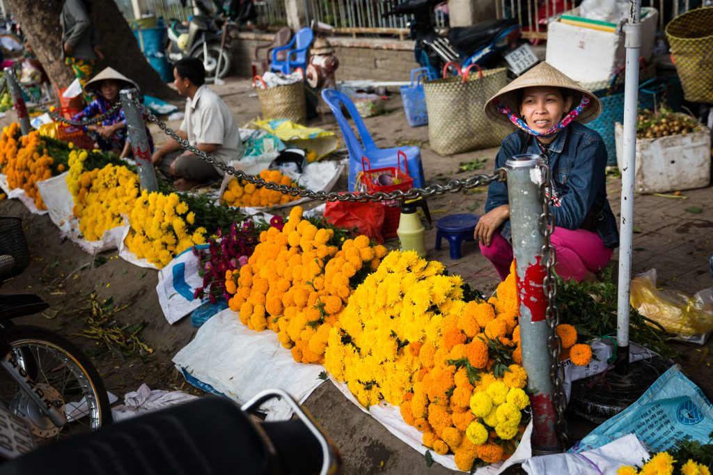 Woman selling marigolds for an article on the Cai Be Floating Markets