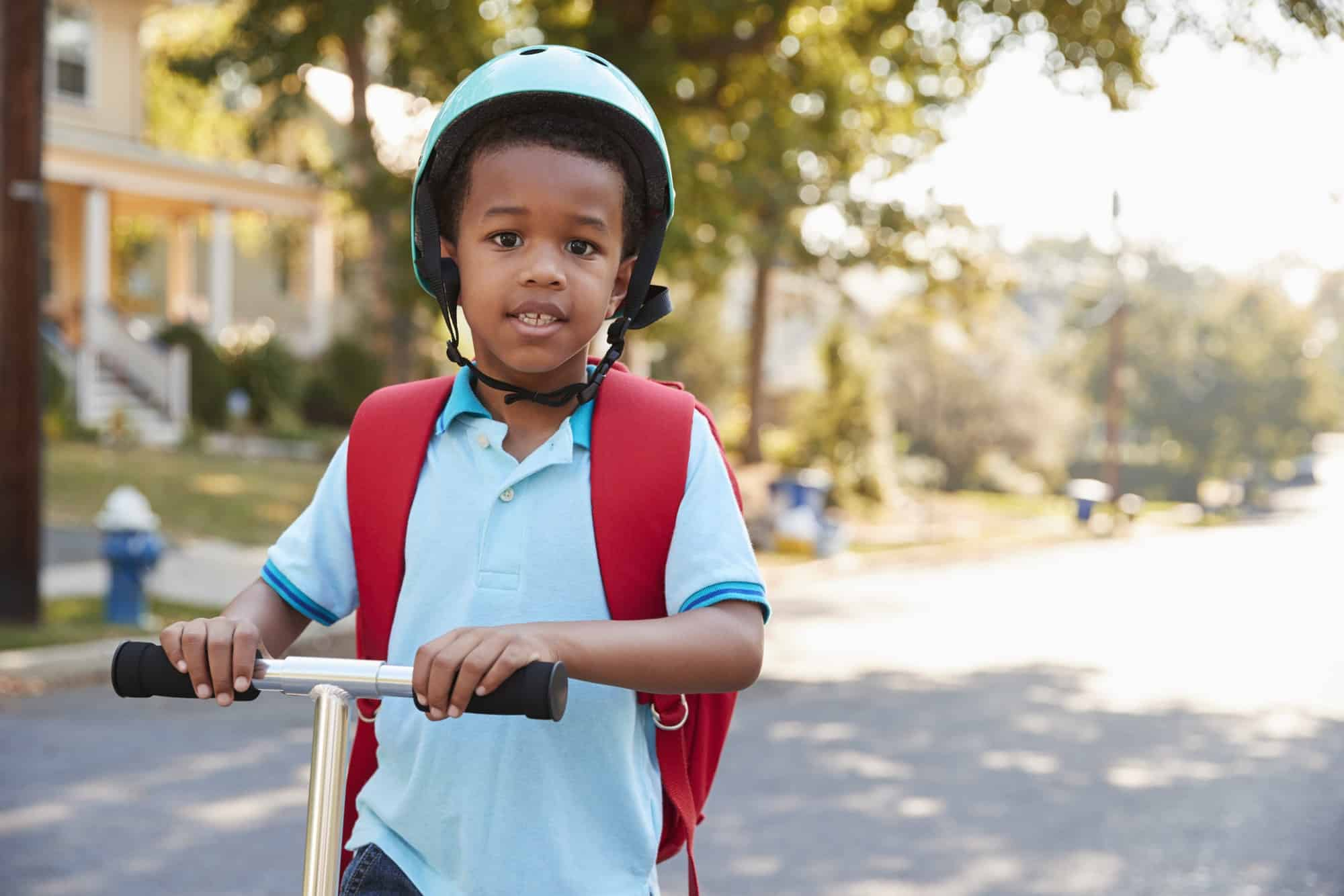 Young Boy Riding Scooter Along Street To School