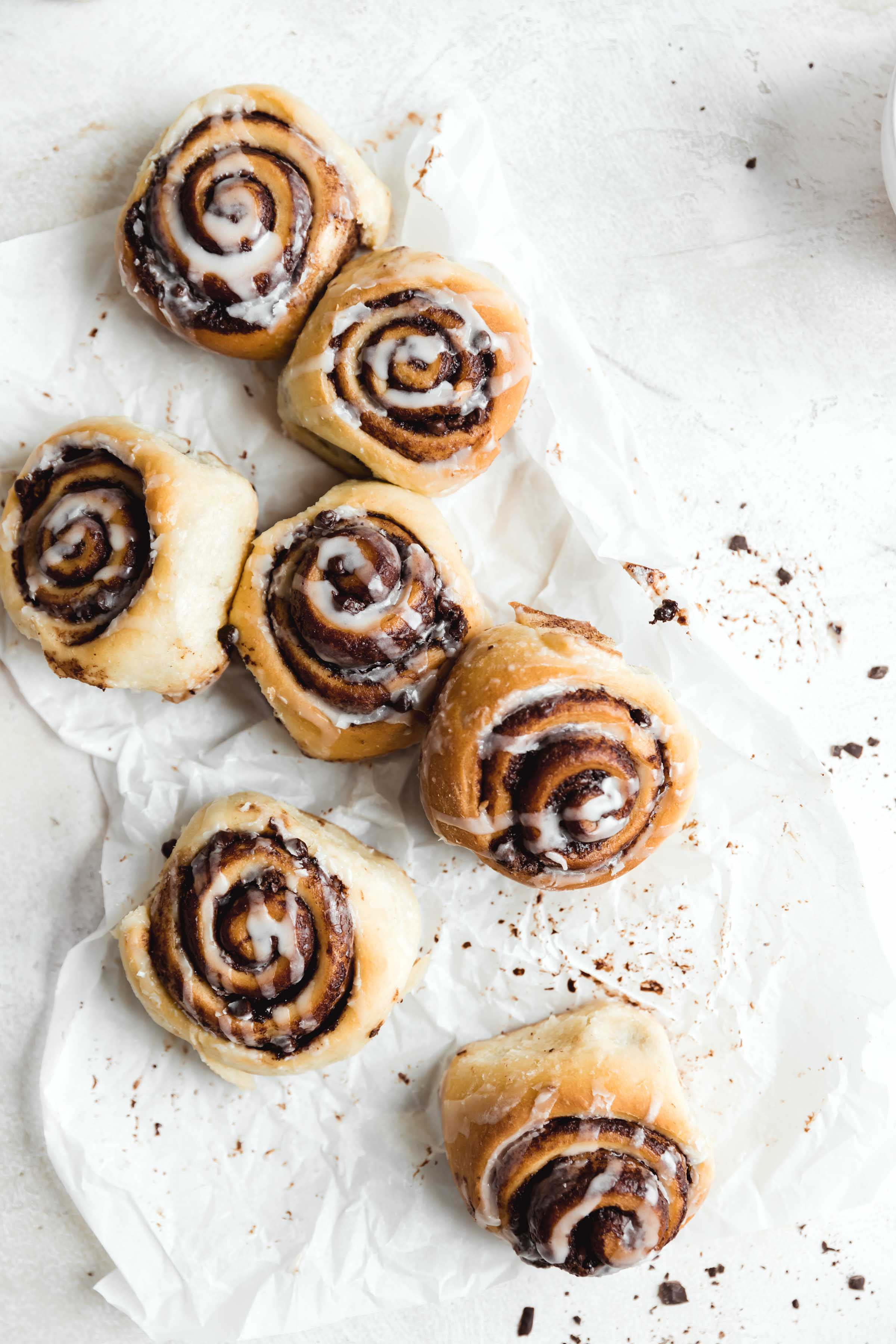 overhead shot of chocolate cinnamon rolls drizzled with cream cheese icing