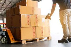 Worker scanning barcode scanner on package boxes on pallet stock photo