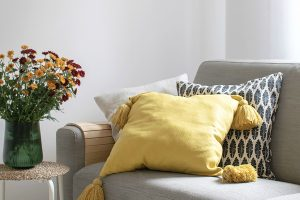 grey sofa with yellow pillows and mums