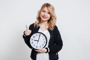 blonde haired woman holding a clock with her thumb up as she's just saved time setting up her life insurance by using a broker