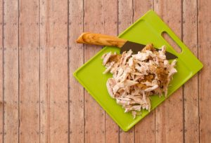 Shredded rotisserie chicken on a green plastic cutting board and carving knife against wood plank background