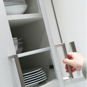 hand opening white cabinet door with plates and bowls inside cabinet