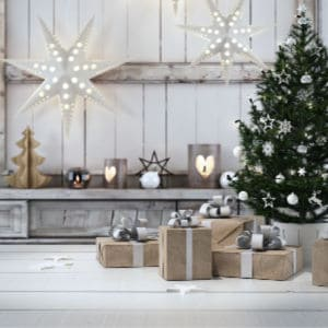 farmhouse style Christmas tree with gifts wrapped in brown paper. simple lighted stars hanging from ceiling.