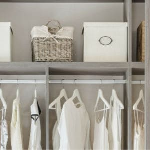 organized closet with neutral colored clothes and storage baskets