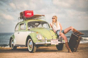 woman sitting on vw bug