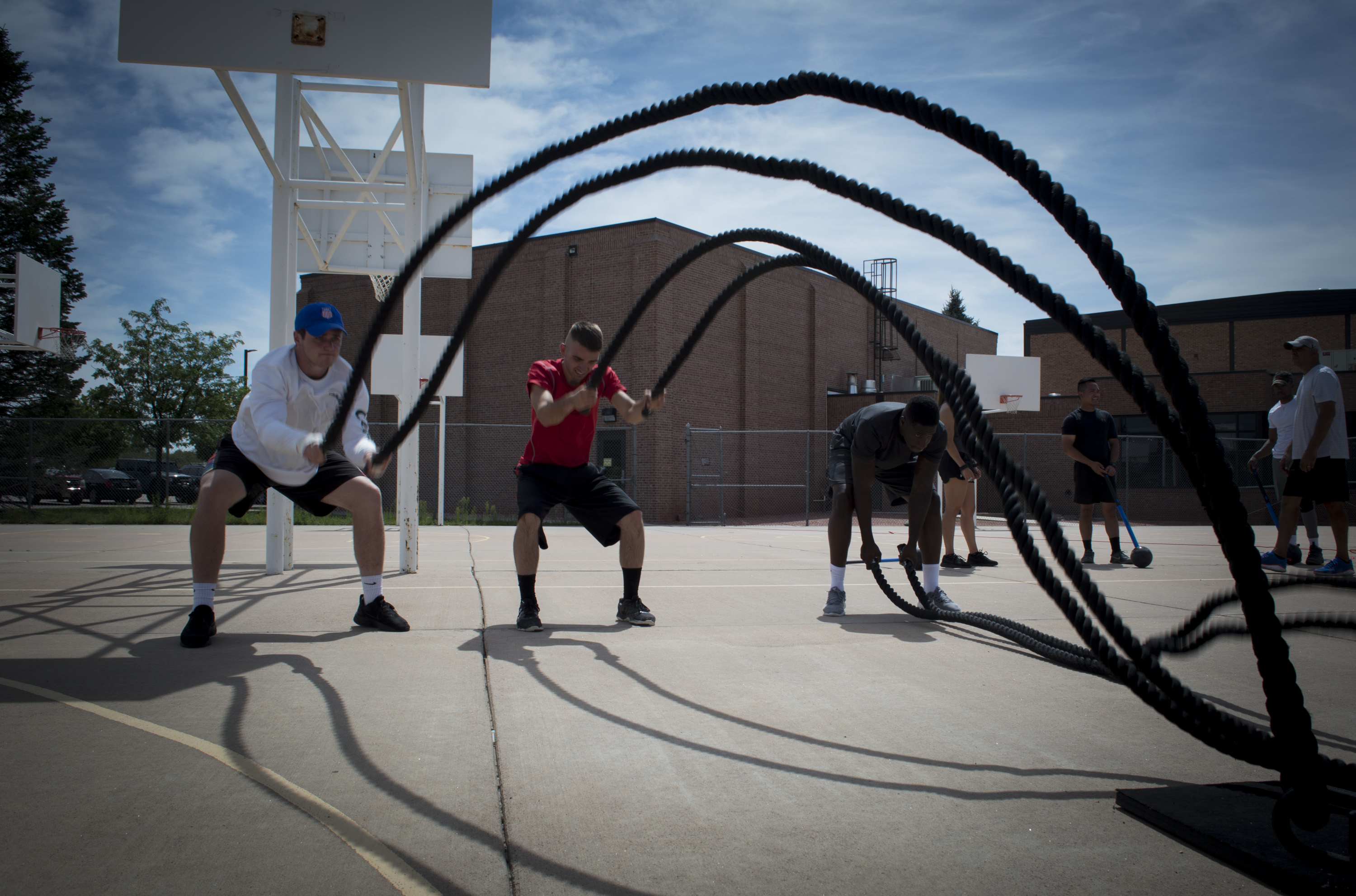 Guys using battle ropes on basketball court