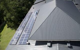 Solar panels on residential home reflecting sunlight.