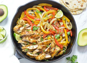 Chicken Fajitas with bell peppers and onions in a black cast iron pan.