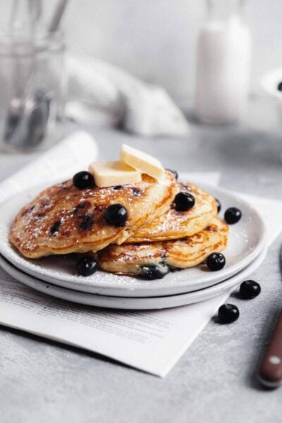 fluffy blueberry pancakes on a plate with maple syrup