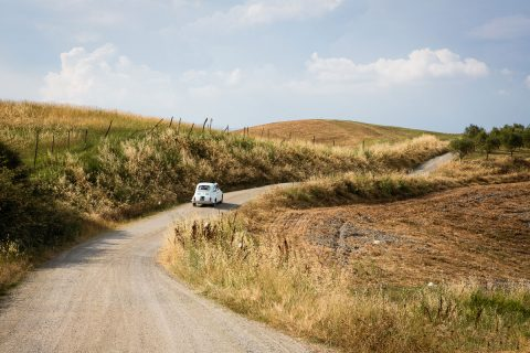 fiat 500 riding on a gravel road in Tuscany