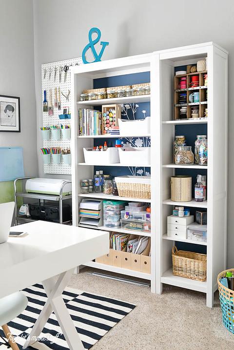 craft supplies organized on white bookcase
