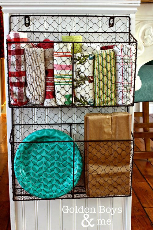 chicken wire baskets mounted to side of kitchen cabinet