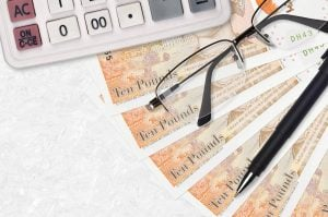 ten pound notes with glasses and calculator
