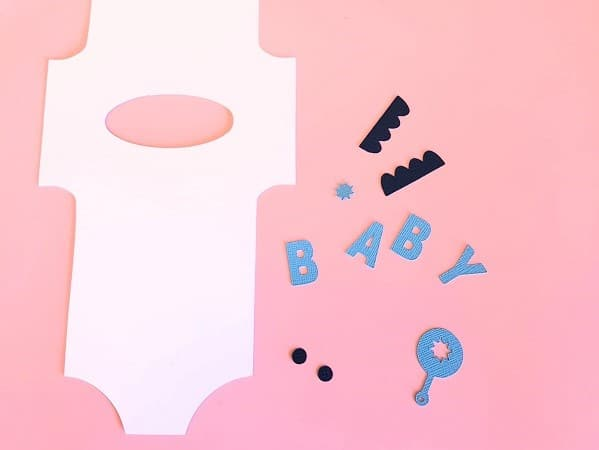 Pieces of the baby romper card ready to be assembled