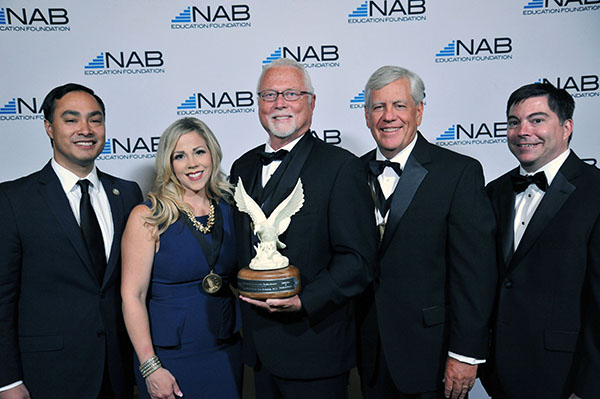 A participant receives a lifetime achievement award from the National Association of Broadcasters during this Washington, DC awards photography event.