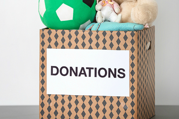 Donation box with toys on table against light background