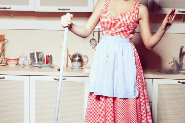 1950s housewife washes the floor in the kitchen.