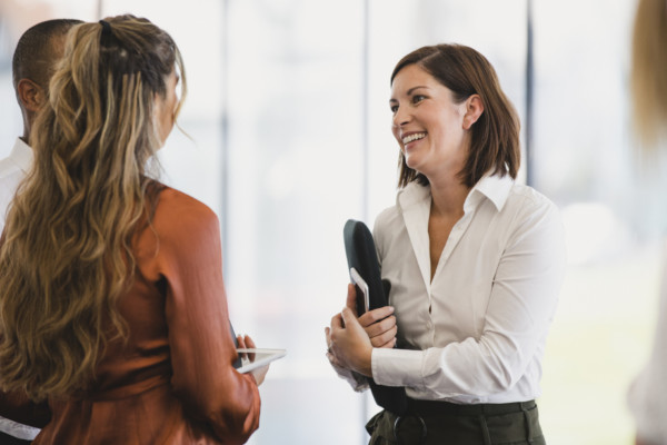 Businesswoman Smiling With Young Colleagues At Work Event
