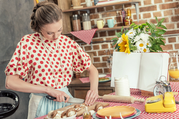 1950's housewife in polka shirt and apron cutting mushrooms in kitchen
