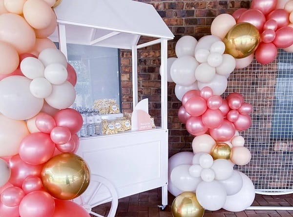 Baby shower decorations with balloons and a quaint pop corn cart.
