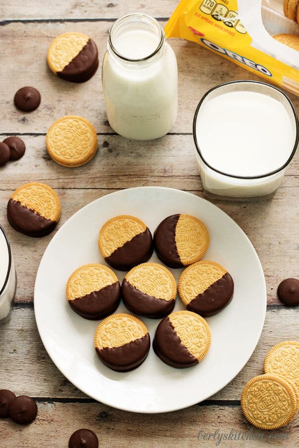Chocolate dipped Oreos on a white plate.