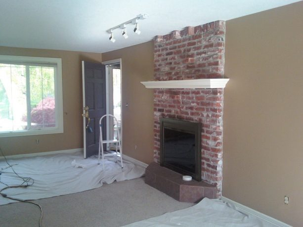before makeover floor to ceiling red brick fireplace with white mantel shelf